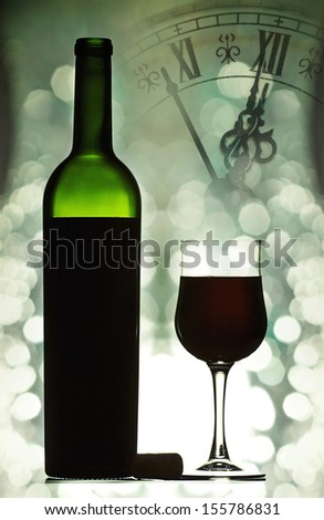 Red wine against holiday lights and clock close to midnight