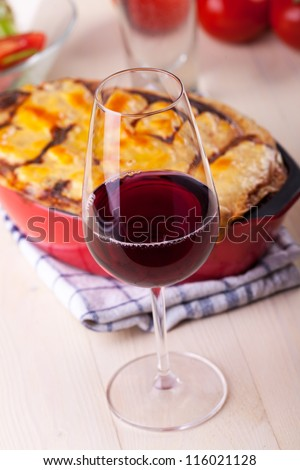 red wine and a bowl of lasagna