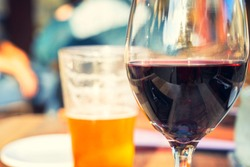 Red wine and beer glass on wooden table with blurry people background