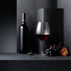 Red wine and blue grapes on a black stone table. Copy space.