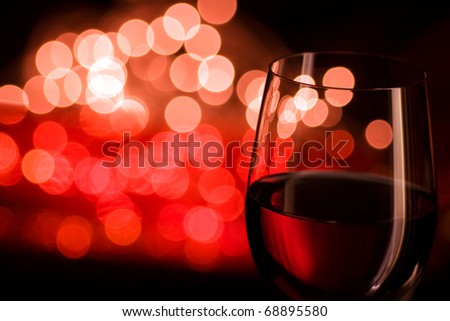 Red wine and blurred lights Shallow depth of field, focus is on the frontal glass line and lamp reflex only.
