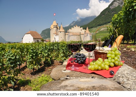 Red wine and grapes against Chateau d'Aigle castle. Switzerland