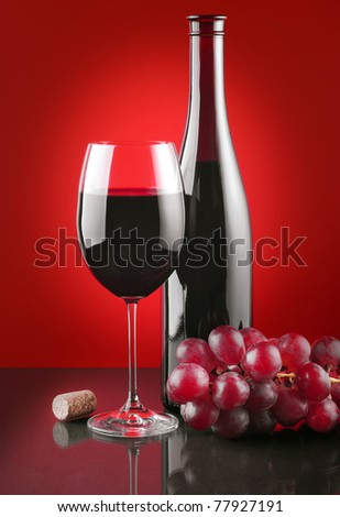 Red wine and ripe fruits of grapes on a glass surface