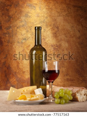 stock-photo-red-wine-assorted-cheeses-bread-and-grapes-in-a-still-life-setup-77517163.jpg
