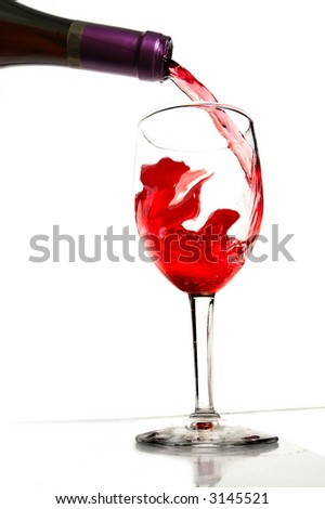 Red wine being poured from a bottle into a glass
