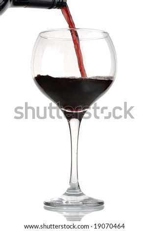 Red wine being poured from bottle into wineglass, isolated against white