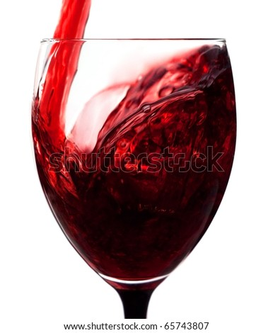 Red wine being poured in a wine glass over white background