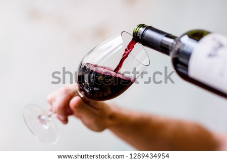 Red wine being poured in to wine glass with blurred background #1289434954