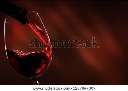 Red wine being poured in wineglass, closeup #1287847009