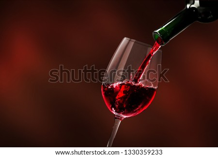 Red wine being poured in wineglass, closeup #1330359233