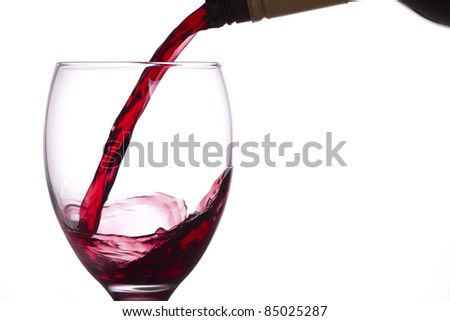 Red wine being poured into a glass from a bottle, white background.
