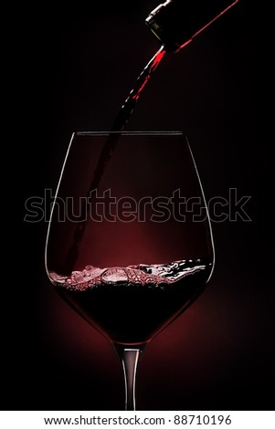 Red wine being poured into wineglass on black background.