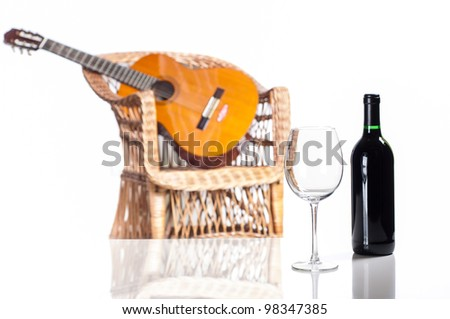 red wine bottle and glass with a guitar on background