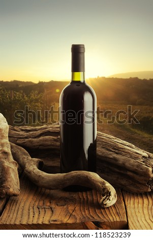 Red wine bottle and old wood, vineyard on background