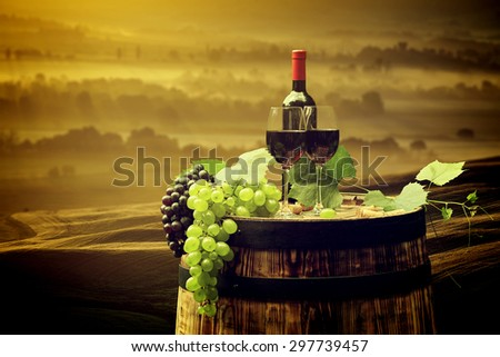 Red wine bottle and wine glass on old barrel. Beautiful Tuscany background