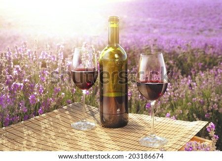 Red wine bottle and wine glass on wodden table.