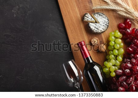 Red wine bottle, bunch of grapes, cheese, ears of wheat and wineglass on wooden board and black background. Top view with copy space. #1373350883