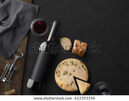Red Wine bottle, corkscrew, cheese, wineglass, bread on black stone background, top view, copy space. Wine bottle mockup. 3d illustration.