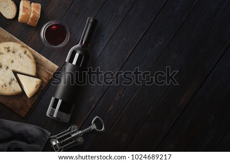 Red Wine bottle, corkscrew, cheese, wineglass, bread on black wood background, top view, copy space. Wine bottle mockup. Top view.  3d illustration.