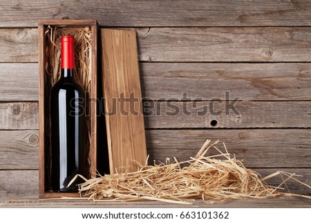 Red wine bottle in box in front of wooden wall. With copy space Stock photo ©