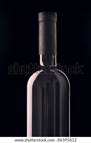 Red wine bottle isolated on black background. - stock photo