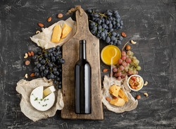 Red wine bottle on vintage cutting wooden board, wine drink mockup. Frame made from Gastronomy of different cheeses grapes honey nuts. Restaurant dinner, wine tasting on dark concrete background