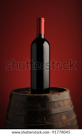 red wine bottle on wodden barrel