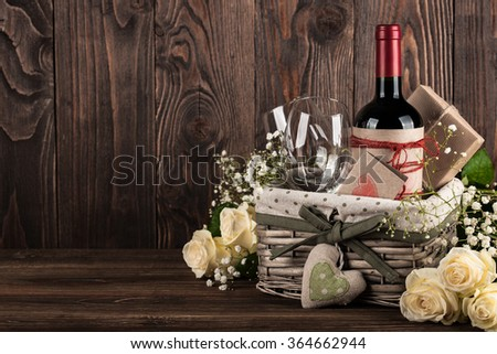 Red wine bottle, two wine glasses, gift boxes in the basket, white roses on the dark wooden background Stock photo ©