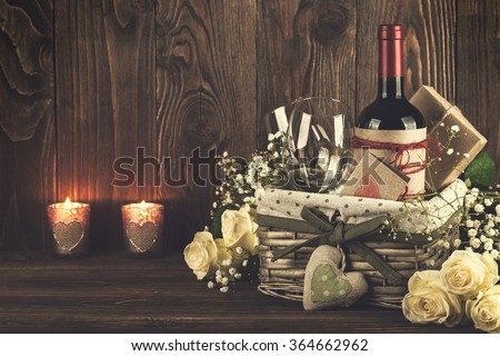 Red wine bottle, two wine glasses, gift boxes in the basket, white roses on the dark wooden background