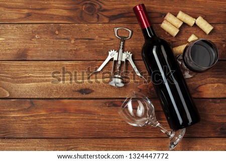 Red wine bottle, wine glass and corkscrew on wooden table background #1324447772
