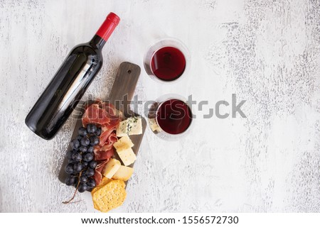 Red wine bottle,wine glasses and charcuterie board with different snacks for wine. Different type of cheese, grapes, cured meat and crackers. Flat-lay Wine background