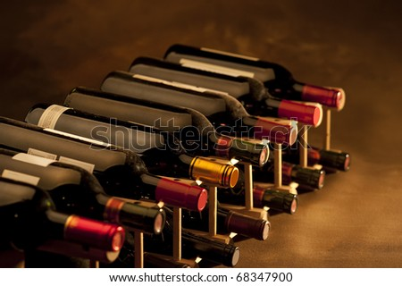 Red wine bottles stacked in rack on warm background - stock photo