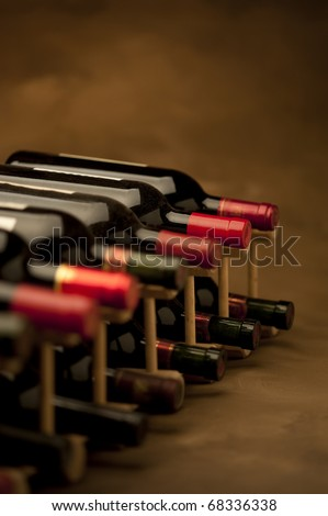 Red wine bottles stacked in rack on warm background, vertical