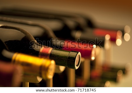 Red wine bottles stacked on wooden racks shot with limited depth of field