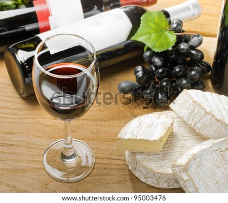 Red wine, Brie, Camembert and grape on the wood surface, studio shot