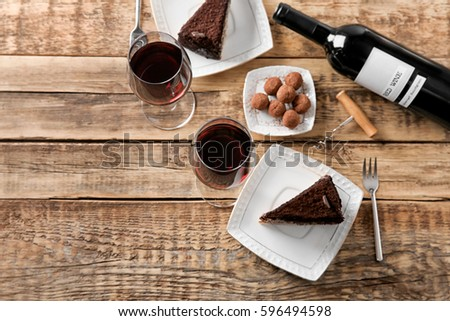Red wine, chocolate truffles and tasty cake on wooden background #596494598