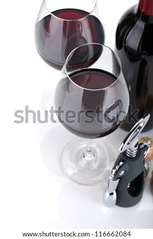 Red wine, corks and corkscrew. Isolated on white background, closeup, focus on glasses.