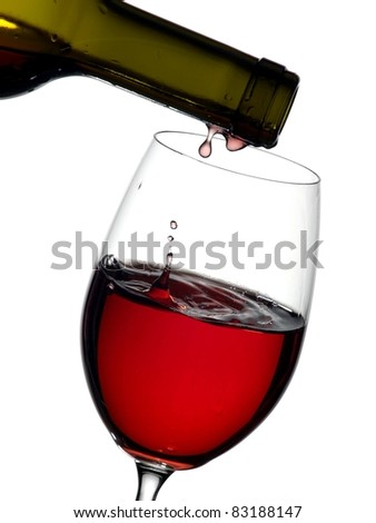 Red wine end pouring in a glass from a green bottle - stock photo