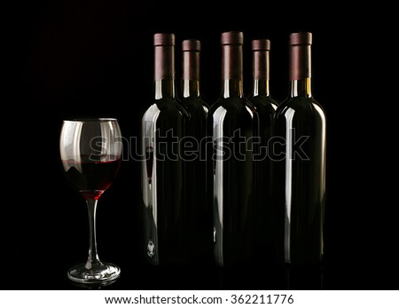 Red wine glass against bottles in a row on black background, close up #362211776