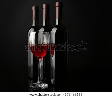Red wine glass against bottles in a row on black background, close up #376466185