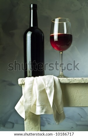 red wine glass and bottle on a with table