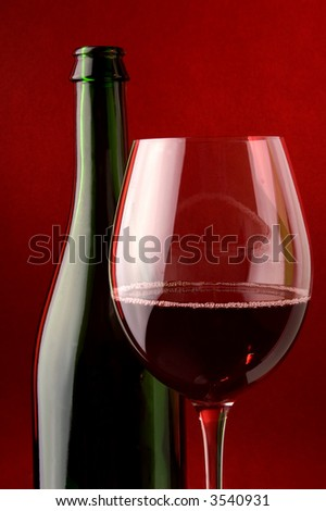 Red wine glass and green wine bottle details.Red background light.