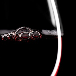 Red Wine Glass silhouette on Black Background with Bubbles