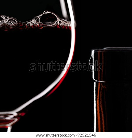 Red Wine Glass silhouette on Black Background with Bubbles and bottleneck with a drop
