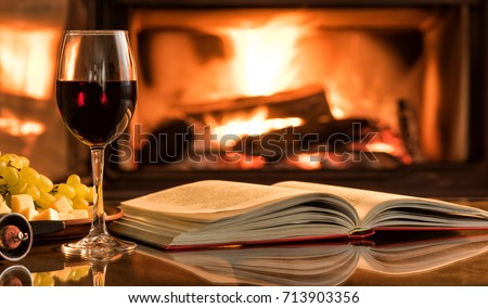 Red wine glass with an open book on table in front of burning fireplace.