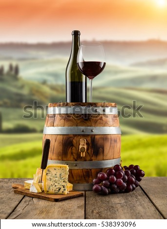 Red wine glass with bottle served on wooden barrel, vineyard on background, copyspace for text