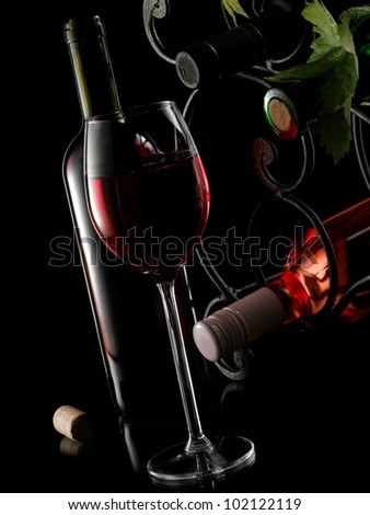 Red wine glass with bottles and wrought iron rack