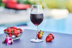 Red wine glass with strawberries on a table on the beach.