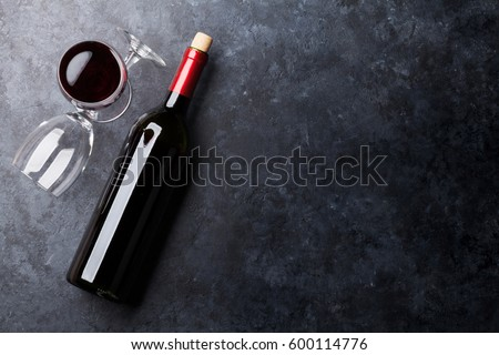 Red wine glasses and bottle on stone background. Top view with copy space #600114776