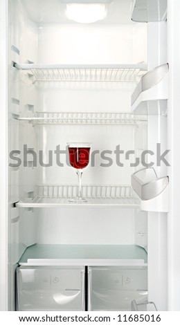 Red wine in a glass in an empty refrigerator